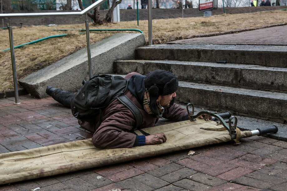 An anti-government protester takes cover from suspected sniper fire near the Hotel Ukraine on February 20, 2014 in Kiev, Ukraine. After several weeks of calm, violence has again flared between anti-government protesters and police, with dozens killed. Photo: Brendan Hoffman, Getty Images