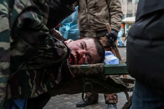 KIEV, UKRAINE - FEBRUARY 20: A wounded anti-government protester is carried to a waiting ambulance on February 20, 2014 in Kiev, Ukraine. After several weeks of calm, violence has again flared between anti-government protesters and police, with dozens killed. (Photo by Brendan Hoffman/Getty Images) Photo: Brendan Hoffman, Getty Images