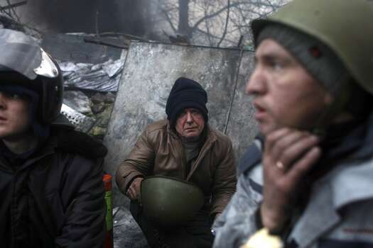 Anti-government protesters pause at  a barricade on the outskirts of Independence Square in Kiev, Ukraine, Thursday, Feb. 20, 2014. Fierce clashes between police and protesters, some including gunfire, shattered a brief truce in Ukraine's besieged capital Thursday, killing numerous people. The deaths came in a new eruption of violence just hours after the country's embattled president and the opposition leaders demanding his resignation called for a truce and negotiations to try to resolve Ukraine's political crisis.  (AP Photo/ Marko Drobnjakovic) Photo: Marko Drobnjakovic, Associated Press