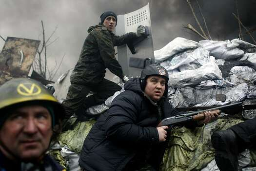 An anti-government protester holds a firearm as he mans a barricade on the outskirts of Independence Square in Kiev, Ukraine, Thursday, Feb. 20, 2014. Fierce clashes between police and protesters, some including gunfire, shattered a brief truce in Ukraine's besieged capital Thursday, killing numerous people. The deaths came in a new eruption of violence just hours after the country's embattled president and the opposition leaders demanding his resignation called for a truce and negotiations to try to resolve Ukraine's political crisis. (AP Photo/ Marko Drobnjakovic) Photo: Marko Drobnjakovic, Associated Press