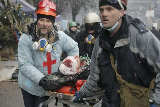 Activists  evacuate a wounded protester during clashes with police in Kiev's Independence Square, the epicenter of the country's current unrest, Kiev, Ukraine, Thursday, Feb. 20, 2014. Fierce clashes between police and protesters, some including gunfire, shattered a brief truce in Ukraine's besieged capital Thursday, killing numerous people. The deaths came in a new eruption of violence just hours after the country's embattled president and the opposition leaders demanding his resignation called for a truce and negotiations to try to resolve Ukraine's political crisis.   (AP Photo/Efrem Lukatsky) Photo: Efrem Lukatsky, Associated Press