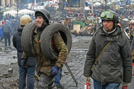 KIEV, UKRAINE - FEBRUARY 20:  Anti-government protesters rebuild barricades following continued clashes with police in Independence square, despite a truce agreed between the Ukrainian president and opposition leaders on February 20, 2014 in Kiev, Ukraine. After several weeks of calm, violence has again flared between police and anti-government protesters, who are calling to oust President Viktor Yanukovych over corruption and an abandoned trade agreement with the European Union  (Photo by Jeff J Mitchell/Getty Images) Photo: Jeff J Mitchell, Getty Images