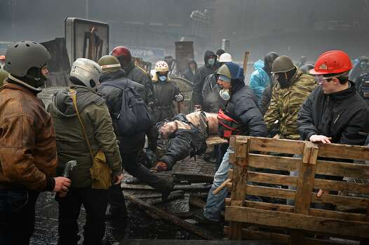 KIEV, UKRAINE - FEBRUARY 20:  Anti-government protesters carry the injured during continued clashes with police in Independence square, despite a truce agreed between the Ukrainian president and opposition leaders on February 20, 2014 in Kiev, Ukraine. After several weeks of calm, violence has again flared between police and anti-government protesters, who are calling to oust President Viktor Yanukovych over corruption and an abandoned trade agreement with the European Union.  (Photo by Jeff J Mitchell/Getty Images) Photo: Jeff J Mitchell, Getty Images