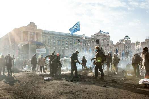 KIEV, UKRAINE - FEBRUARY 20: Anti-governent protesters clear ashes and debris from a newly occupied portion of Independence Square on February 20, 2014 in Kiev, Ukraine.  Dozens of protesters were reportedly been killed after violence flared again between police and anti-government protesters, who are calling to oust President Viktor Yanukovych over corruption and an abandoned trade agreement with the European Union.  (Photo by Brendan Hoffman/Getty Images) Photo: Brendan Hoffman, Getty Images