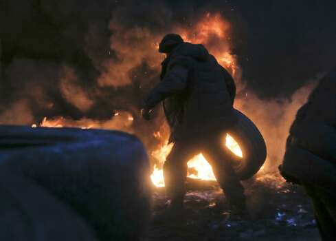 An activist carries a tyre at the burning barricades close to Independence Square, the epicenter of the country's current unrest, in Kiev, Ukraine, Thursday, Feb. 20, 2014. Fierce clashes between police and protesters in Ukraine's capital have shattered the brief truce Thursday and an Associated Press reporter has seen dozens bodies laid out on the edge of the protest encampment.  (AP Photo/Efrem Lukatsky) Photo: Efrem Lukatsky, Associated Press