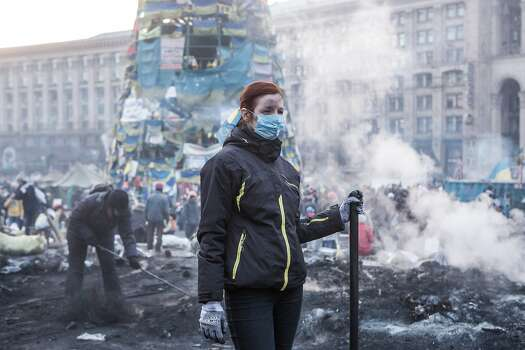KIEV, UKRAINE - FEBRUARY 20: A woman clears ashes and debris with other anti-government protesters from a newly-occupied portion of Independence Square on February 20, 2014 in Kiev, Ukraine. Dozens of protesters were reportedly been killed after violence flared again between police and anti-government protesters, who are calling to oust President Viktor Yanukovych over corruption and an abandoned trade agreement with the European Union.  (Photo by Brendan Hoffman/Getty Images) Photo: Brendan Hoffman, Getty Images