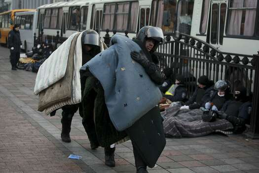 Police officers carry mattresses to take a rest at Ukraine's parliament in Kiev, Ukraine, Thursday, Feb. 20, 2014. Ferocious street battles between protesters and police in the Ukrainian capital have left dozens dead and hundreds wounded in the past few days, raising fears that the ex-Soviet nation, whose loyalties are split between Russia and the West, is in an uncontrollable spiral of violence.(AP Photo/Petro Zadorozhnyy) Photo: Petro Zadorozhnyy, Associated Press