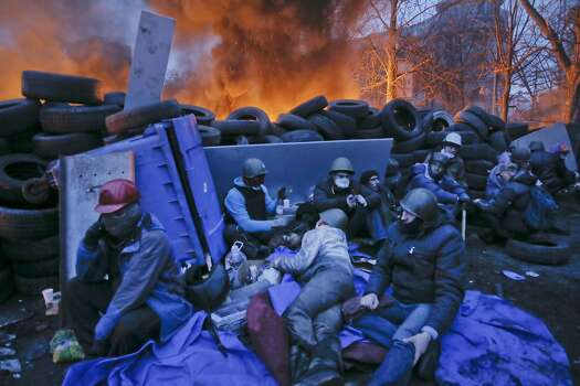 Activists have a rest at the burning barricades, on the side of bloody clashes close to Independence Square, the epicenter of the country's current unrest, Kiev, Ukraine, Thursday, Feb. 20, 2014. Fearing that a call for a truce was a ruse, protesters tossed firebombs and advanced upon police lines Thursday in Ukraine's embattled capital. Government snipers shot back and the almost medieval melee that ensued left scores of people dead. (AP Photo/Efrem Lukatsky) Photo: Efrem Lukatsky, Associated Press