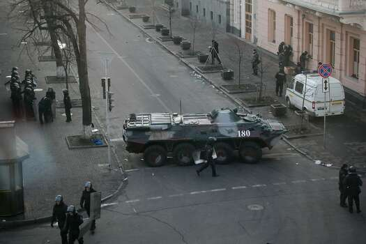 Police block the way with an armored personnel carrier at the Ukraine's parliament in Kiev, Ukraine, Thursday, Feb. 20, 2014. Ferocious street battles between protesters and police in the Ukrainian capital have left dozens dead and hundreds wounded in the past few days, raising fears that the ex-Soviet nation, whose loyalties are split between Russia and the West, is in an uncontrollable spiral of violence.(AP Photo/Petro Zadorozhnyy) Photo: Petro Zadorozhnyy, Associated Press