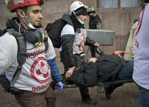 An anti-government protester wounded by firearms is carried to a makeshift clinic in central Kiev, Ukraine, Thursday, Feb. 20, 2014. A brief truce in Ukraine's embattled capital failed Thursday, spiraling into fierce clashes between police and anti-government protesters. (AP Photo/Darko Bandic) Photo: Darko Bandic, Associated Press