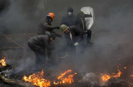 Anti-government protesters reinforce a barricade in central Kiev, Ukraine, Thursday, Feb. 20, 2014. A brief truce in Ukraine's embattled capital failed Thursday, spiraling into fierce clashes between police and anti-government protesters. (AP Photo/Darko Bandic) Photo: Darko Bandic, Associated Press
