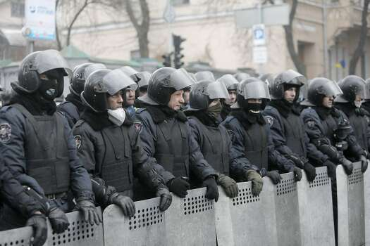 Police officers block a street near the Cabinet of Ministers offies in the center of Kiev, Ukraine, Thursday, Feb. 20, 2014. Fierce clashes between police and protesters, some including gunfire, shattered a brief truce in Ukraine's besieged capital Thursday, killing numerous people. The deaths came in a new eruption of violence just hours after the country's embattled president and the opposition leaders demanding his resignation called for a truce and negotiations to try to resolve Ukraine's political crisis. (AP Photo/Efrem Lukatsky) Photo: Efrem Lukatsky, Associated Press