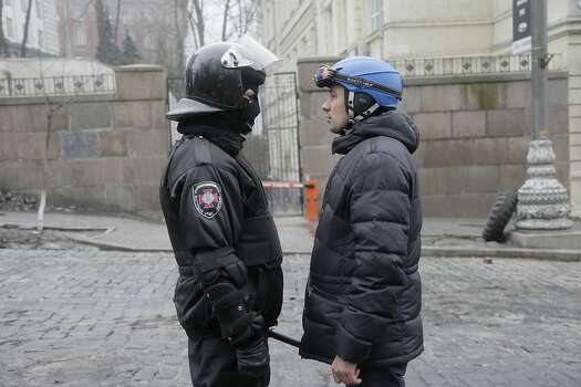 A high-ranking police officer, left, and a protester representative hold talks near the Cabinet of Ministers in the center  Kiev, Ukraine, Thursday, Feb. 20, 2014. Fierce clashes between police and protesters, some including gunfire, shattered a brief truce in Ukraine's besieged capital Thursday, killing numerous people. The deaths came in a new eruption of violence just hours after the country's embattled president and the opposition leaders demanding his resignation called for a truce and negotiations to try to resolve Ukraine's political crisis. (AP Photo/Efrem Lukatsky) Photo: Efrem Lukatsky, Associated Press