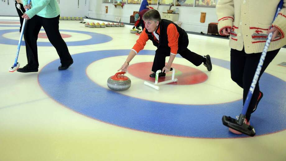 "Marianne Roggemann, of Shelton, delivers the stone during a round of curling Wednesday, Feb. 19, 2014 at the Nutmeg Curling Club in Bridgeport, Conn.  Roggemann started playing 6 years ago, inspired by the Olympics. ""I thought - that's a sport I can do,"" she said. Photo: Autumn Driscoll / Connecticut Post"
