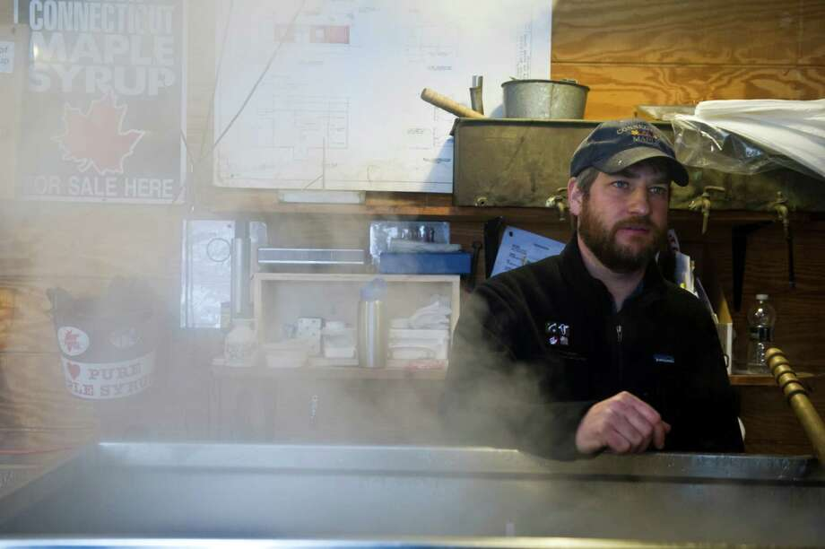 Will Kies, director of education at the Stamford Museum and Nature Center, stands in the fog of an evaporator as the center hosts a previous Maple Sugar Festival Weekend in Stamford, Conn. This year's festival is set for March 1 and 2, 2014. For more information, visit www.stamfordmuseum.org or call 203-322-1646. Photo: Keelin Daly / Stamford Advocate