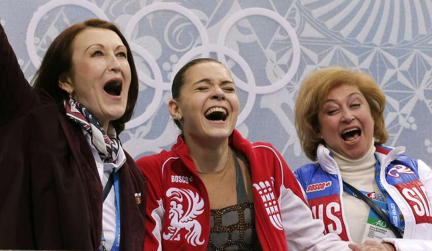 Adelina Sotnikova of Russia, centre, her coach Elena Buianova, right, and choreographer Irina Tagaeva react in the results area after she completed her routine in the women's free skate figure skating finals at the Iceberg Skating Palace during the 2014 Winter Olympics, Thursday, Feb. 20, 2014, in Sochi, Russia.