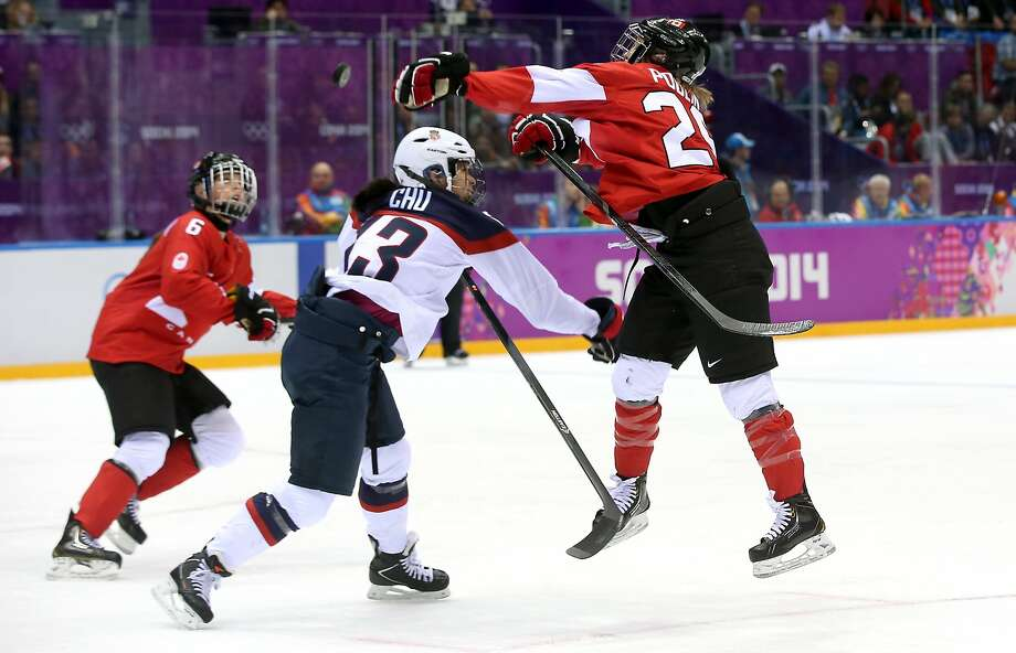 Julie Chu #13 of the United States checks Marie-Philip Poulin #29 of Canada during the Ice Hockey Women's Gold Medal Game on day 13 of the Sochi 2014 Winter Olympics at Bolshoy Ice Dome on February 20, 2014 in Sochi, Russia.  Photo: Bruce Bennett, Getty Images