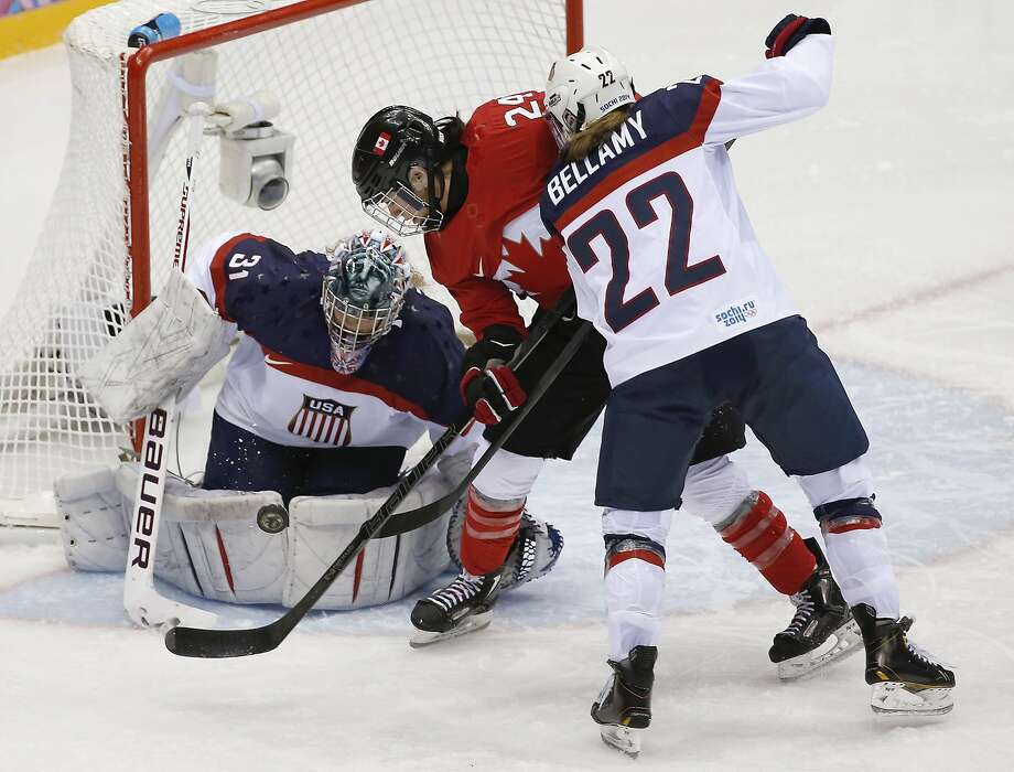 USA goalkeeper Jessie Vetter (31) blocks Natalie Spooner of Canada's (24) shot on the goal as Kacey Bellamy of the United States (22) skates in to help defend during the third period of the women's gold medal ice hockey game at the 2014 Winter Olympics, Thursday, Feb. 20, 2014, in Sochi, Russia. (AP Photo/Petr David Josek) Photo: Petr David Josek, Associated Press