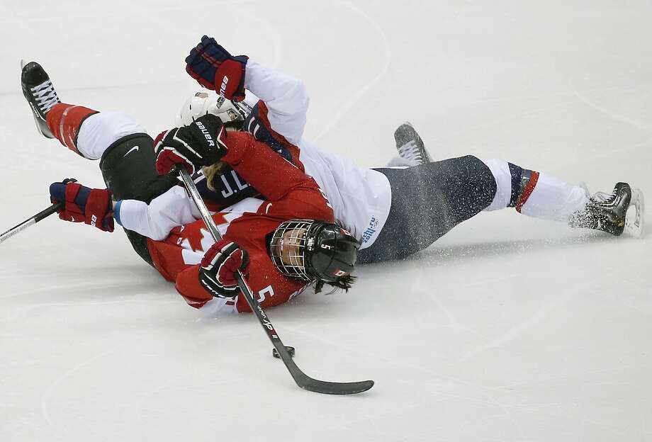 Lauriane Rougeau of Canada (5) collides with Jocelyne Lamoureux of the United States (17) during the third period of the women's gold medal ice hockey game at the 2014 Winter Olympics, Thursday, Feb. 20, 2014, in Sochi, Russia. (AP Photo/Julio Cortez) Photo: Julio Cortez, Associated Press