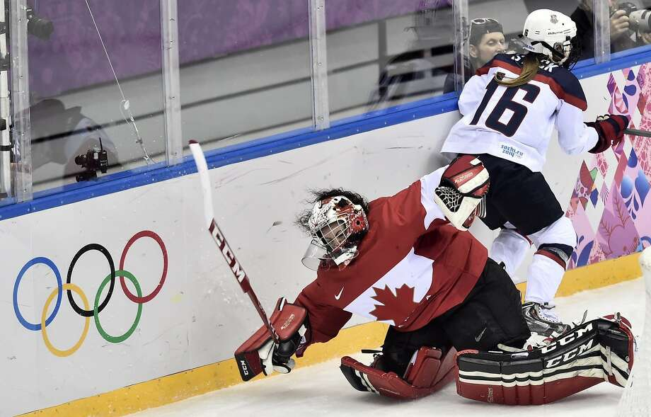 Canada's goalie Shannon Szabados is tripped up by Kelli Stack of the United States during the second period of the women's gold medal ice hockey game at the 2014 Winter Olympics, Thursday, Feb. 20, 2014, in Sochi, Russia. (AP Photo/The Canadian Press, Nathan Denette) Photo: Nathan Denette, Associated Press