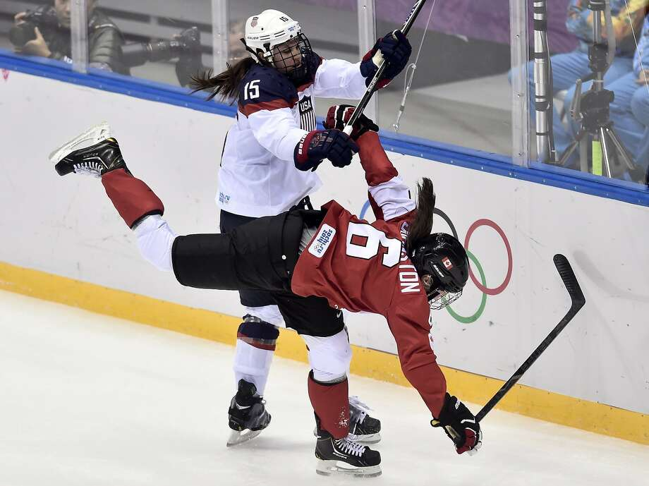 Anne Schleper of the Untied States, left,  takes down Rebecca Johnston of Canada during the second period of the women's gold medal ice hockey game at the 2014 Winter Olympics, Thursday, Feb. 20, 2014, in Sochi, Russia. (AP Photo/The Canadian Press, Nathan Denette) Photo: Nathan Denette, Associated Press
