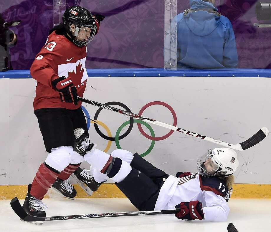 Caroline Ouellette, of Canada, left, checks Jocelyne Lamoureux, of the United States during the second period of the women's gold medal ice hockey game at the 2014 Winter Olympics, Thursday, Feb. 20, 2014, in Sochi, Russia. (AP Photo/The Canadian Press, Nathan Denette) Photo: Nathan Denette, Associated Press