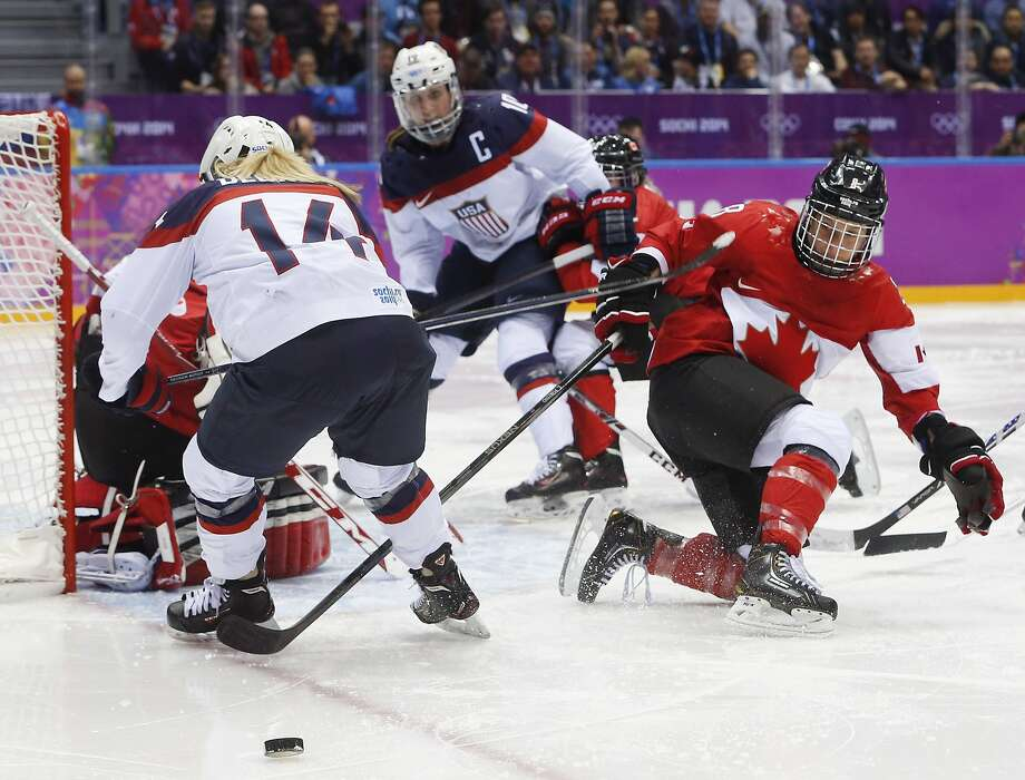 Brianna Decker of the United States (14) and Laura Fortino of Canada (8) look for a rebound during the third period of the women's gold medal ice hockey game at the 2014 Winter Olympics, Thursday, Feb. 20, 2014, in Sochi, Russia. (AP Photo/Mark Humphrey) Photo: Mark Humphrey, Associated Press