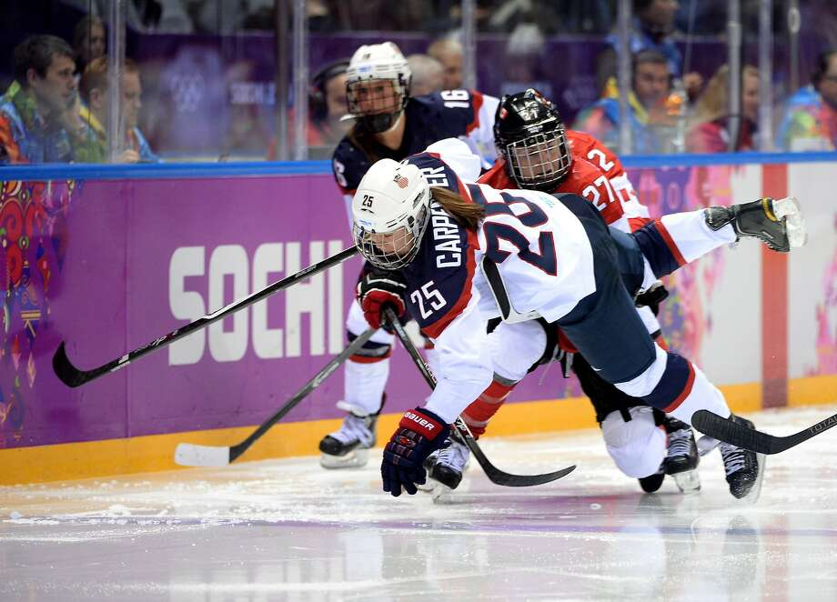 Alex Carpenter #25 of the United States falls to the ice against Tara Watchorn #27 of Canada during the Ice Hockey Women's Gold Medal Game on day 13 of the Sochi 2014 Winter Olympics at Bolshoy Ice Dome on February 20, 2014 in Sochi, Russia. Photo: Harry How, Getty Images