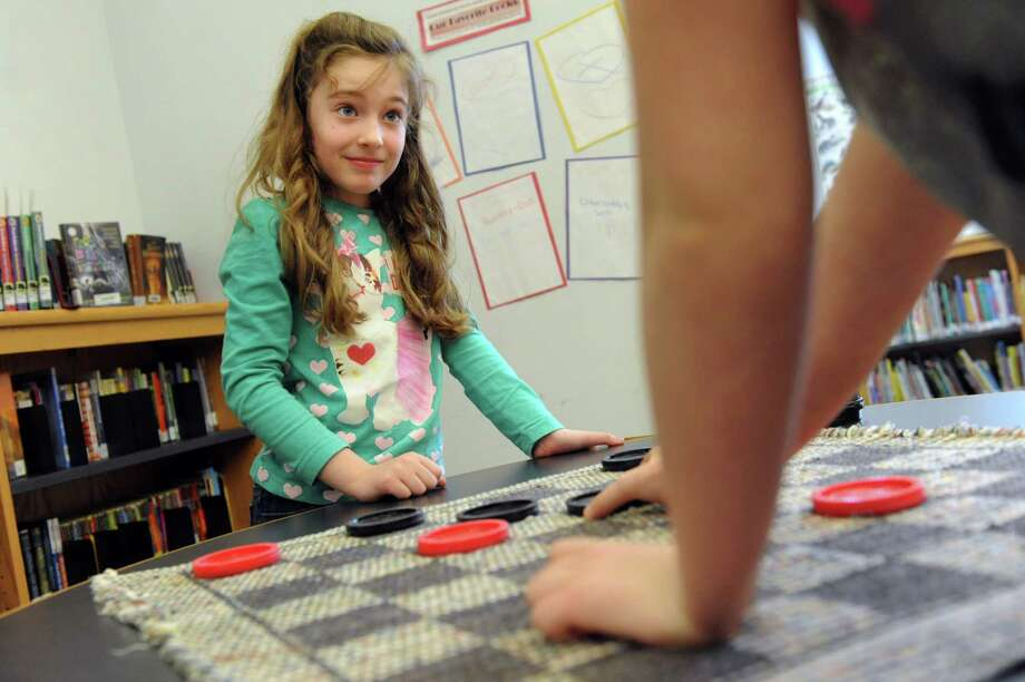 Rachel Sheumaker, 8, left, waits for fellow camper, Aimee Louttit, 9, to make her move as they play checkers on Tuesday, Feb. 18, 2014, at Malta Community Center in Malta, N.Y. The girls are attending Go Kids Winter Camp for art activities, games and gym time. The camp, for ages 5 to 9, is from 9 a.m. to 4 p.m. this week and still has openings. (Cindy Schultz / Times Union) Photo: Cindy Schultz / 00025775A