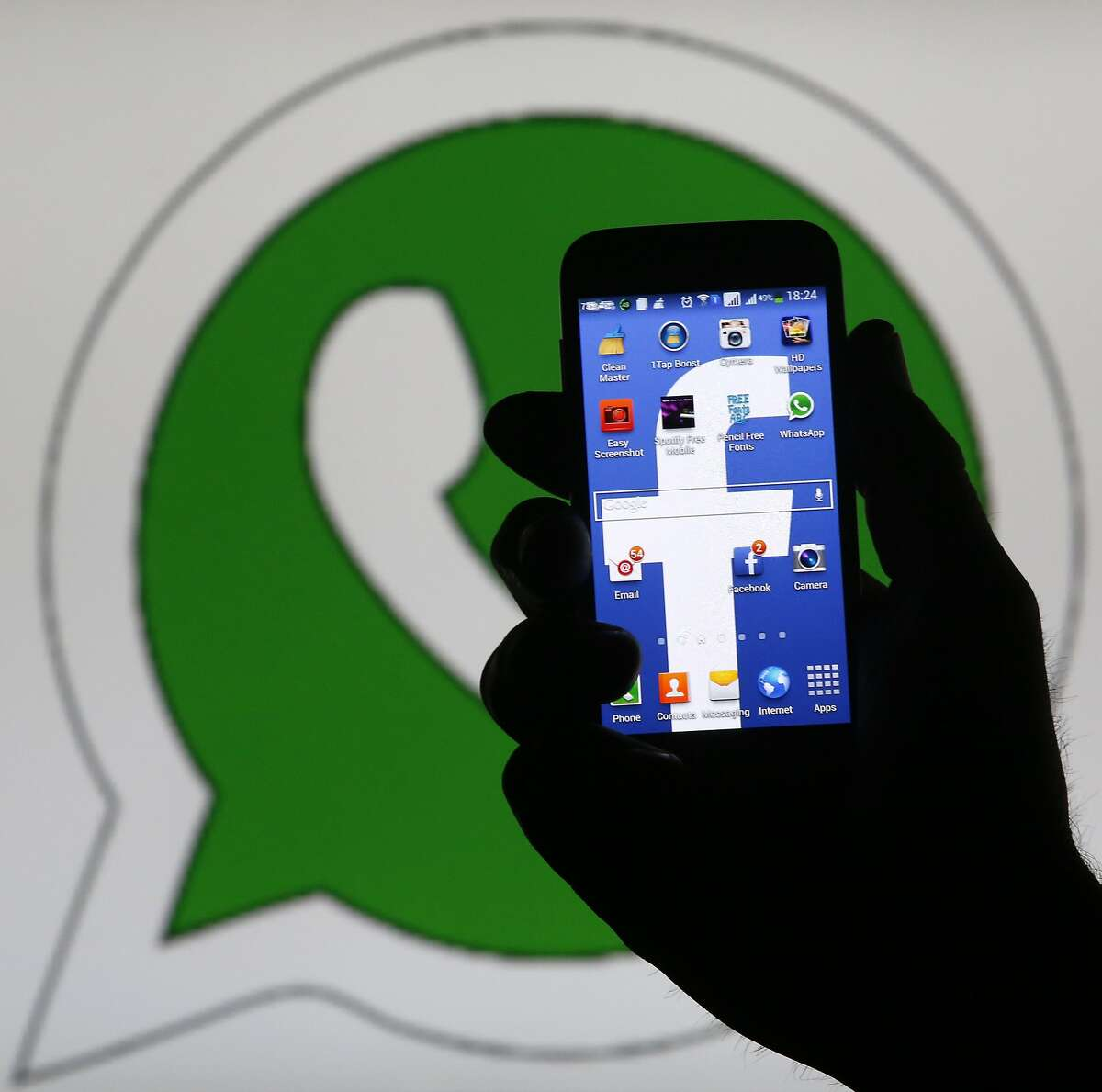 An illustration photo shows a man holding a smart phone with a Facebook logo as its screen wallpaper in front of a WhatsApp messenger logo, in Zenica February 20, 2014. Facebook Inc will buy fast-growing mobile-messaging startup WhatsApp for $19 billion in cash and stock in a landmark deal that places the world's largest social network closer to the heart of mobile communications and may bring younger users into the fold. REUTERS/Dado Ruvic (BOSNIA AND HERZEGOVINA - Tags: SCIENCE TECHNOLOGY BUSINESS)