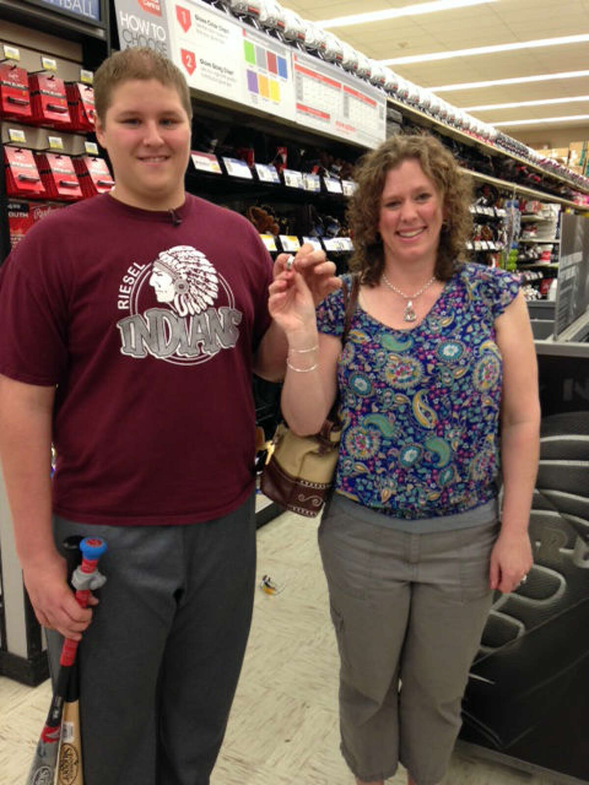 Ryan Alexander, left, and Rebecca Rumsey show the wedding ring he found in his new baseball glove.