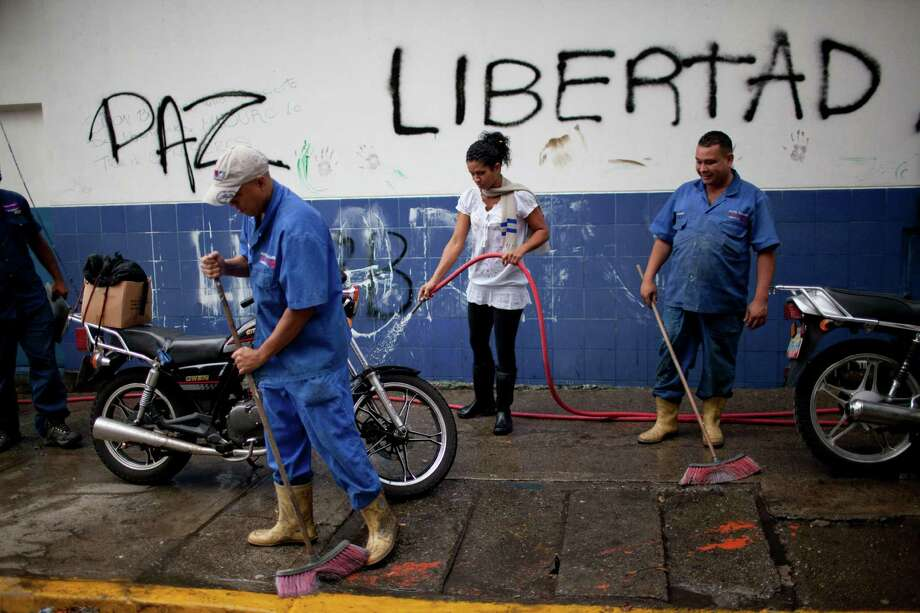 "Workers clean the street  from debris left over from yesterday's clashes between anti government protestors and police in Caracas, Venezuela, Thursday, Feb. 20, 2014. The graffiti on the wall reads in Spanish ""Peace and Liberty"". Violence is heating up in Venezuela as an opposition leader Leopoldo Lopez, faces criminal charges for organizing a rally that set off a deadly week of turmoil in anti-government protests in Caracas and other cities where demonstrators and government forces clashed leaving several dead and scores of wounded. Photo: Rodrigo Abd, AP / AP"
