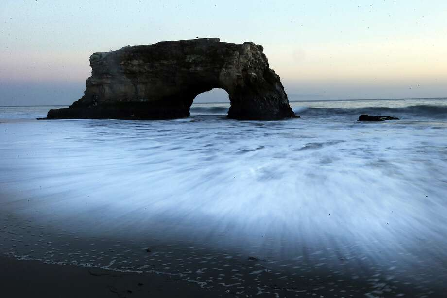 A long exposure makes waves seem like mist at Natural Bridges State Beach in Santa Cruz, 