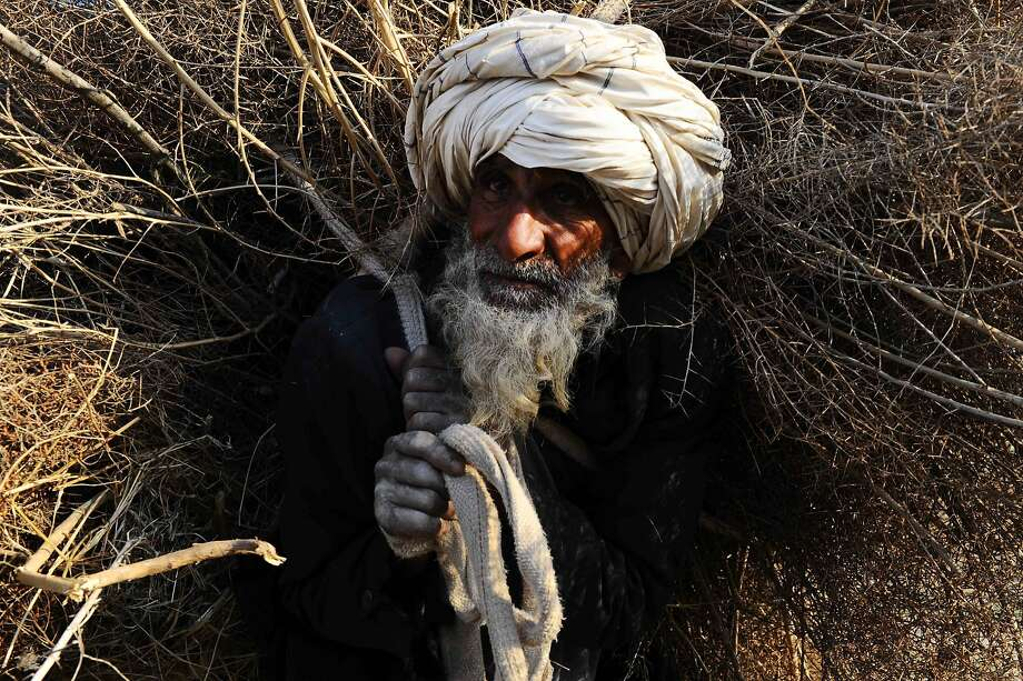 An elderly man lugsa huge pile of kindling in Herat, Afghanistan. Some 9 million 