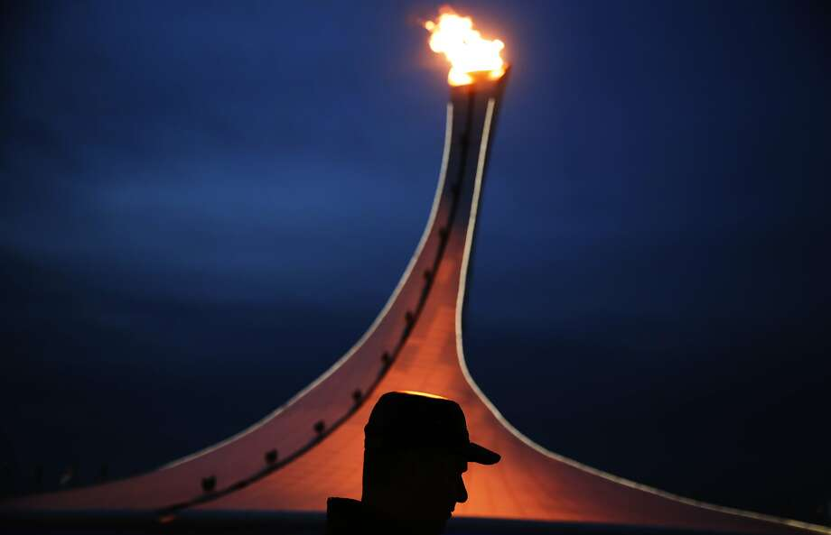 A visitor to Olympic Park is silhouetted while walking past the Olympic cauldron at the 2014 Winter Olympics, Thursday, Feb. 20, 2014, in Sochi, Russia. (AP Photo/David Goldman) Photo: David Goldman, Associated Press