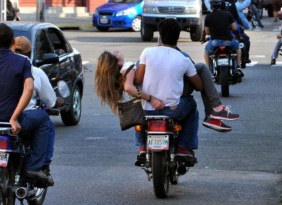 Too late to save her: Genesis Carmona is evacuated by motorcycle after she was wounded during an anti-government protest in Valencia, Venezuela. Carmona was struck by a bullet when unknown 
