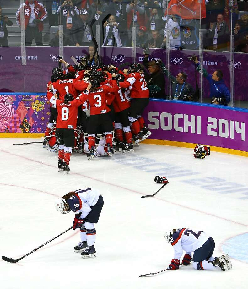Marie-Philip Poulin #29 of Canada celebrates with teammates after scoring the game-winning goal against the United States in overtime as Anne Schleper #15 and Michelle Picard #23 of the United States react during the Ice Hockey Women's Gold Medal Game on day 13 of the Sochi 2014 Winter Olympics at Bolshoy Ice Dome on February 20, 2014 in Sochi, Russia.  Photo: Doug Pensinger, Getty Images