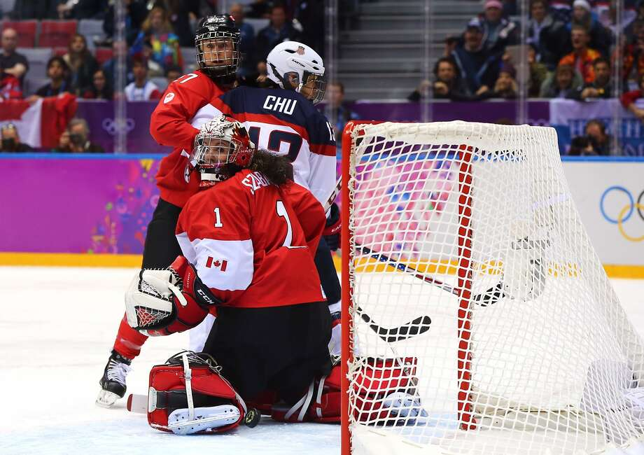 Julie Chu #13 of the United States celebrates with teammates after Meghan Duggan #10 scored a second-period goal against Shannon Szabados #1 of Canada during the Ice Hockey Women's Gold Medal Game on day 13 of the Sochi 2014 Winter Olympics at Bolshoy Ice Dome on February 20, 2014 in Sochi, Russia.  Photo: Martin Rose, Getty Images
