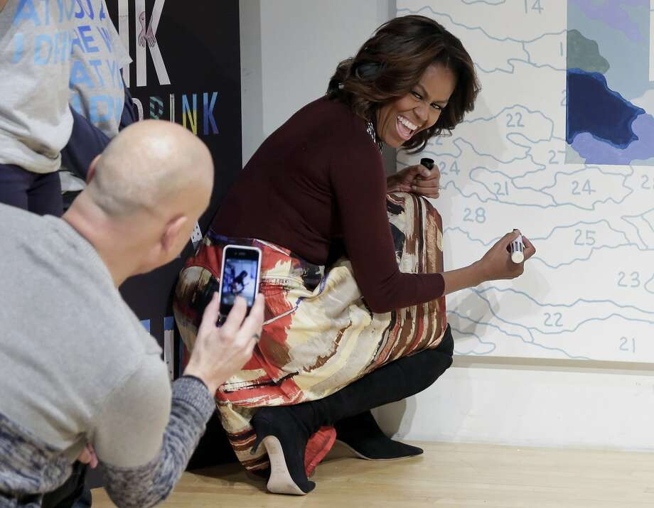 Smile, Ms. Obama! Artist Trey Speegle photographs the first lady as she prepares to autograph his color-by-numbers mural featuring the slogan for WAT-AAH, a line of bottled water targeting kids and teens, at the New Museum in New York. Photo: Richard Drew, Associated Press