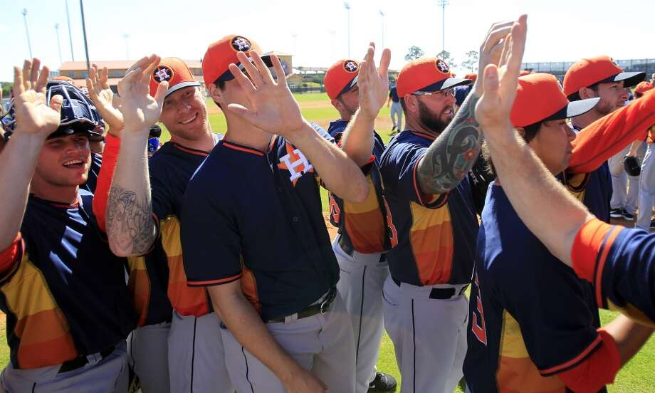 "Astros players high-five each other during the ""shaking hands/ stros win!"" portion of the first full-squad workout. Photo: Karen Warren, Houston Chronicle"
