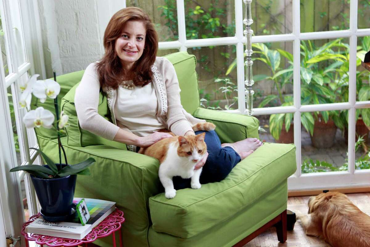 Bettina Siegel poses with the family cat, Clementine, and dog, Piper, in her Houston home Wednesday, Feb. 19, 2014. She has a petition on change.org protesting a US policy that involves shipping US chicken to China for processing, then back to the US for us to eat. ( Melissa Phillip / Houston Chronicle )