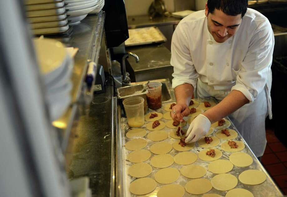Garry Agosto makes beef empanadas at Baró New World Cantina, a Latin American restaurant in the Brick Walk in Fairfield, Conn.  Agosto estimates that the chefs at Baró make 100 empanadas per day at the restaurant. Photo: Autumn Driscoll / Connecticut Post