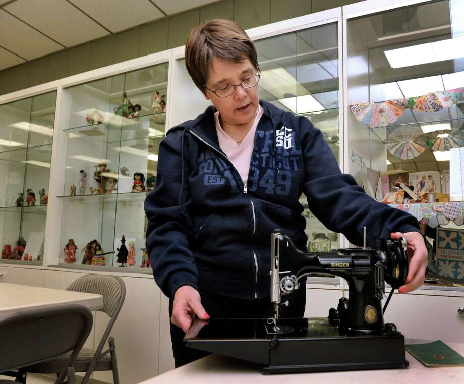 Roni Gerhardt of Danbury, Conn., with a 1957 Feather Weight Singer Sewing Machine that is part of her exhibit at the Danbury Museum and Historical Society Thursday, Feb. 20, 2014. The museum is exhibiting the collections of 18 different local people. Photo: Carol Kaliff / The News-Times