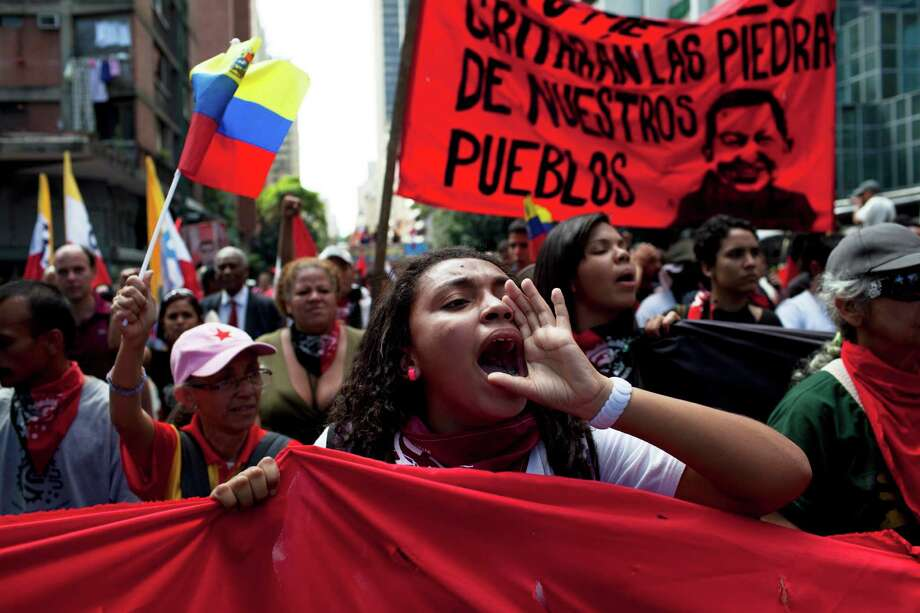 "Members of a pro-government ""colectivo,"" or ""collective,"" march in downtown Caracas, Venezuela, Thursday, Feb. 20, 2014. President Nicolas Maduro and his supporters say the escalating protests against his socialist government in the oil-rich but economically struggling country are part of an attempted coup sponsored by right-wing and ""fascist"" opponents in Venezuela and abroad, particularly the United States. Photo: Rodrigo Abd, AP / AP"