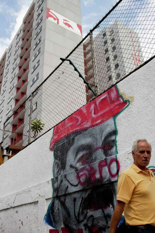 A man walks next to a graffiti with the portrait of Venezuela's President Nicolas Maduro in downtown in Caracas, Venezuela,Thursday, Feb. 20, 2014. Violence is heating up in Venezuela as an opposition leader Leopoldo Lopez, faces criminal charges for organizing a rally that set off a deadly week of turmoil in anti-government protests in Caracas and other cities where demonstrators and government forces clashed leaving several dead and scores of wounded. Photo: Rodrigo Abd, AP / AP