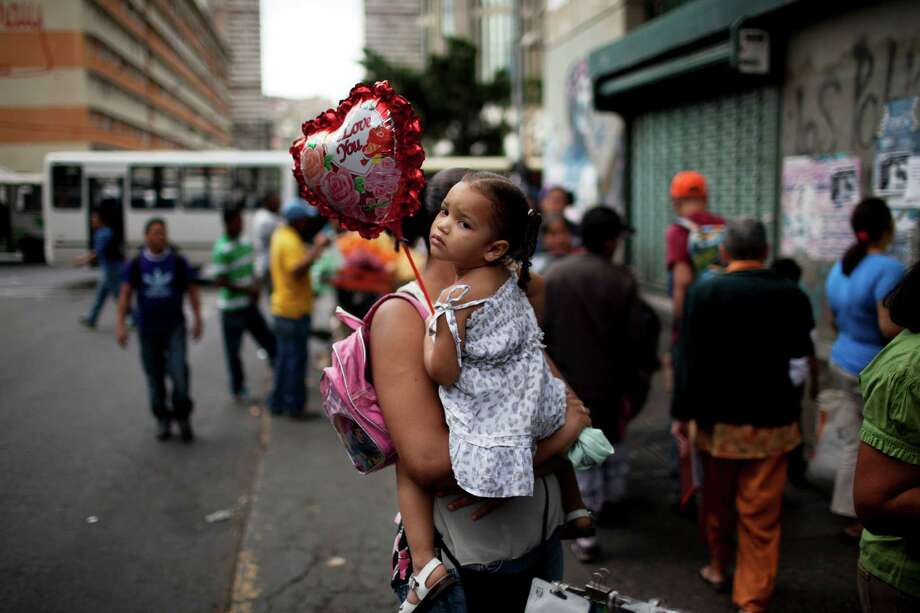 Maria Ramirez holds a balloon in the arms of her mother downtown in Caracas, Venezuela, Thursday, Feb. 20, 2014. Violence is heating up in Venezuela as an opposition leader Leopoldo Lopez, faces criminal charges for organizing a rally that set off a deadly week of turmoil in anti-government protests in Caracas and other cities where demonstrators and government forces clashed leaving several dead and scores of wounded. Photo: Rodrigo Abd, AP / AP
