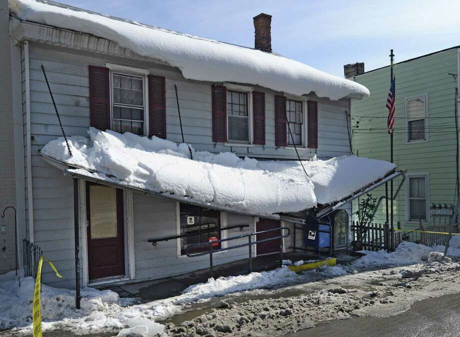 The overhang at 96 Main Street collapses from the weight of the snow Thursday afternoon, Feb. 20, 2014, in Coeymans, N.Y.  The building houses the post office for Coeymans and was shut down after the partial collapse of the overhang. (Skip Dickstein / Times Union) Photo: Skip Dickstein