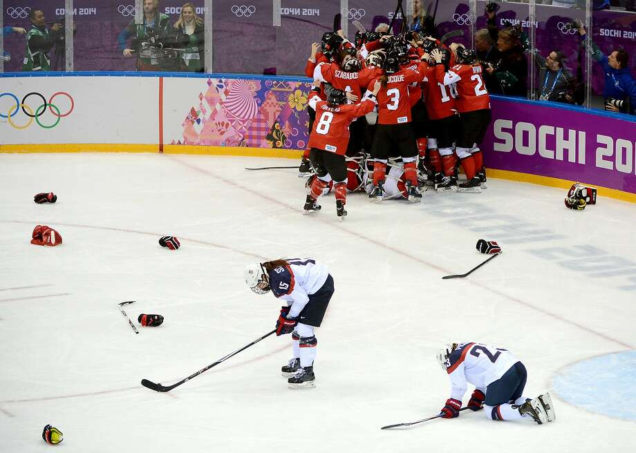 As Canadian players celebrate, Team USA defensemen Anne Schleper (15) and Michelle Picard (23) react to the overtime loss. Photo: Chuck Myers, McClatchy-Tribune News Service