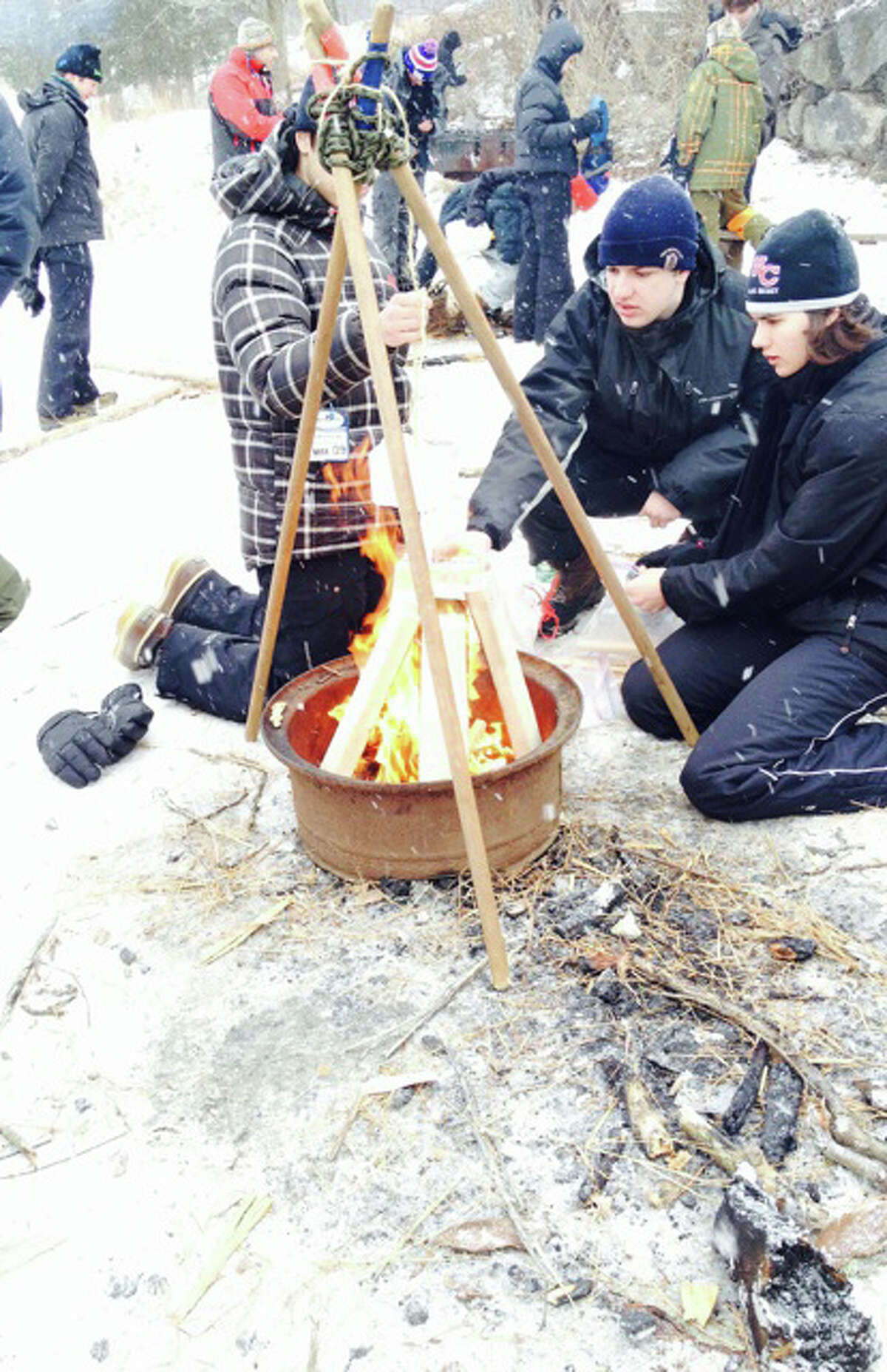 Fire building was an important skill to know to survive the extreme cold weather during Greenwich Scouting's annual Klondike Derby. Above, from left, Troop 37 Scouts Anthony Shaw, Matthew Baptist and Eugene Constandaki use their fire-building skills to melt a block of ice left .
