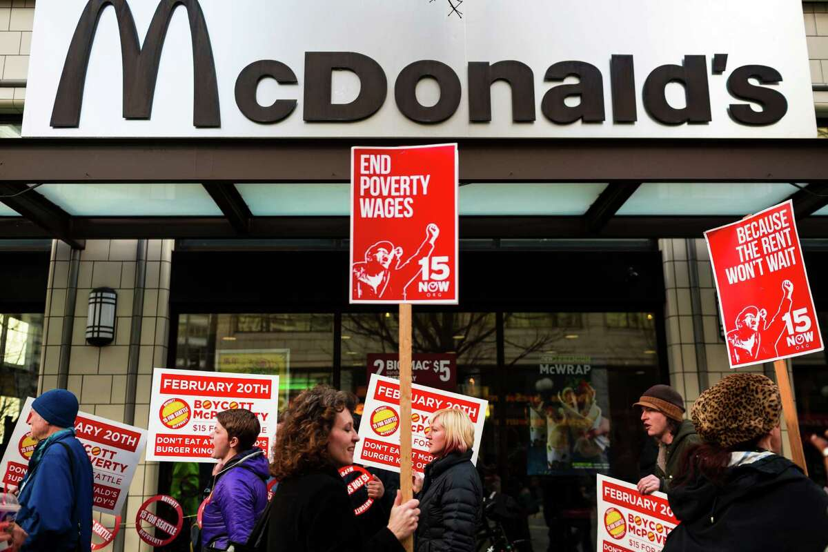 A crowd of Working Washington supporters protesting for 15 dollar minimum wage took to the space in front of McDonald's on 3rd Avenue and Pine Street to hoist signs and chant for improved pay Thursday, Feb. 20, 2014, in downtown Seattle. Seattle City Council member Kshama Sawant joined in to speak, amongst others.
